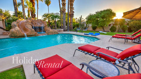 Pool side view with lawn chairs, water slide and also the spa area