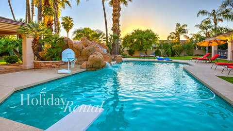 Pool side view with lawn chairs, water slide, spa area along with diving board and basket ball hop