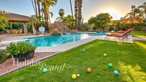 Pool side view with lawn chairs, water slide, spa area and also bocce ball