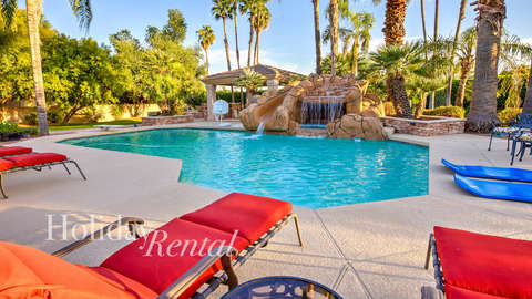 Pool side view of the relaxing lawn chairs along with the pools water fall that is a spa